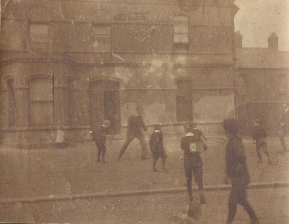 Image labelled 'H.G. Studdart Kennedy', which appears to show him kicking football with young people in front of the Mission building, RCB Library MS 295
